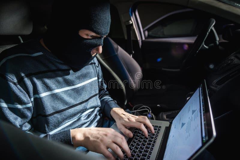 Voleur avec un ordinateur portable à l'intérieur d'une voiture photo libre de droits