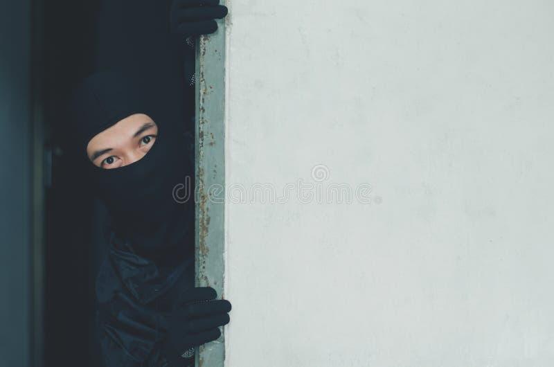 Voleur d'homme, voleur dans le masque se cachant derrière un mur vide avec l'espace pour le texte photos stock