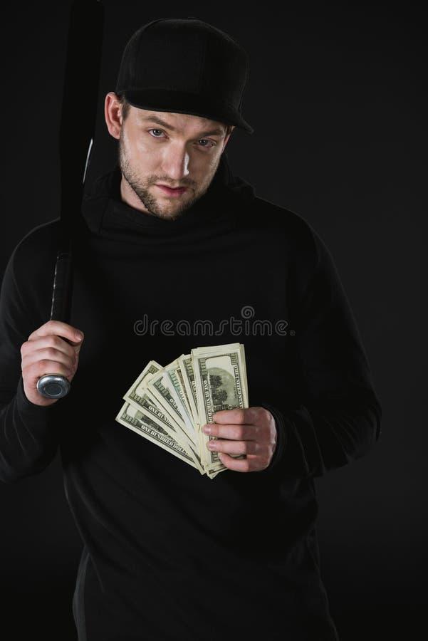 Voleur dans le zoodie avec la batte de baseball et l'argent d'isolement sur le noir photos stock