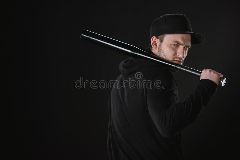 Voleur dans le zoodie et chapeau avec la batte de baseball d'isolement sur le noir images stock