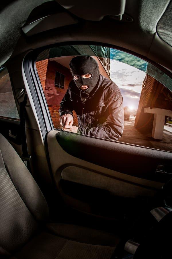 Voleur de voiture dans un masque images stock