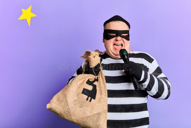Voleur dodu drôle avec un sac tenant une torche et l'employant comme le microphone photo stock