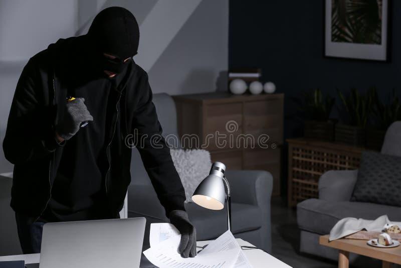 Voleur masculin avec la lampe-torche recherchant des documents à l'intérieur image stock