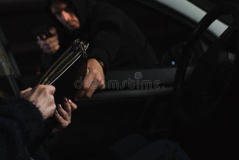 voleur masculin dans le hoodie noir visant par l'arme à feu et volant le sac de la femme images stock