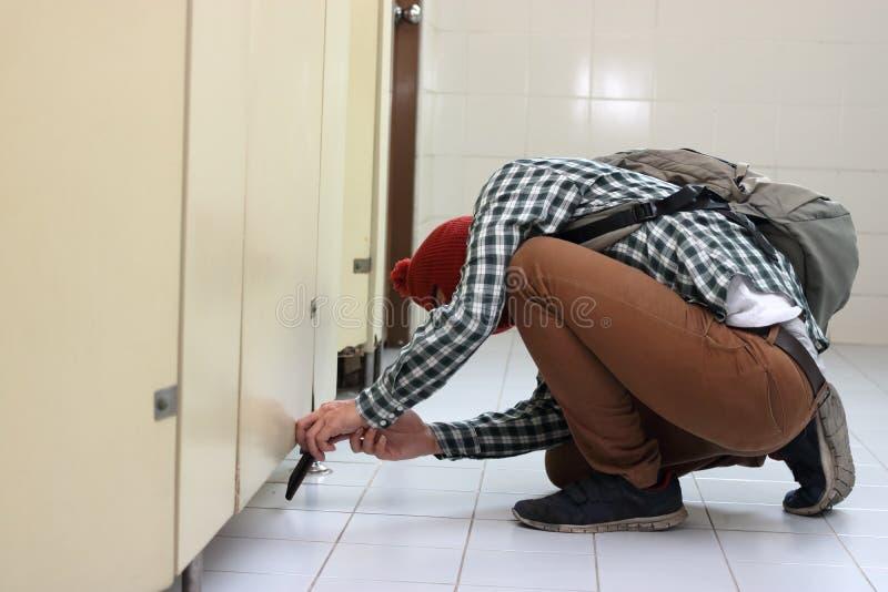 Voleur masqué avec un passe-montagne partant furtivement et prenant une photo avec le téléphone intelligent mobile dans la toilet images stock