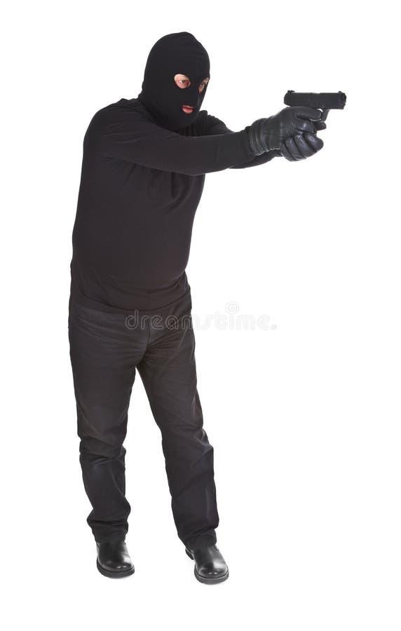 Voleur orientant avec son canon photo stock