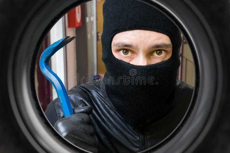 Voleur ou cambrioleur derrière la porte Vue de trou photos libres de droits