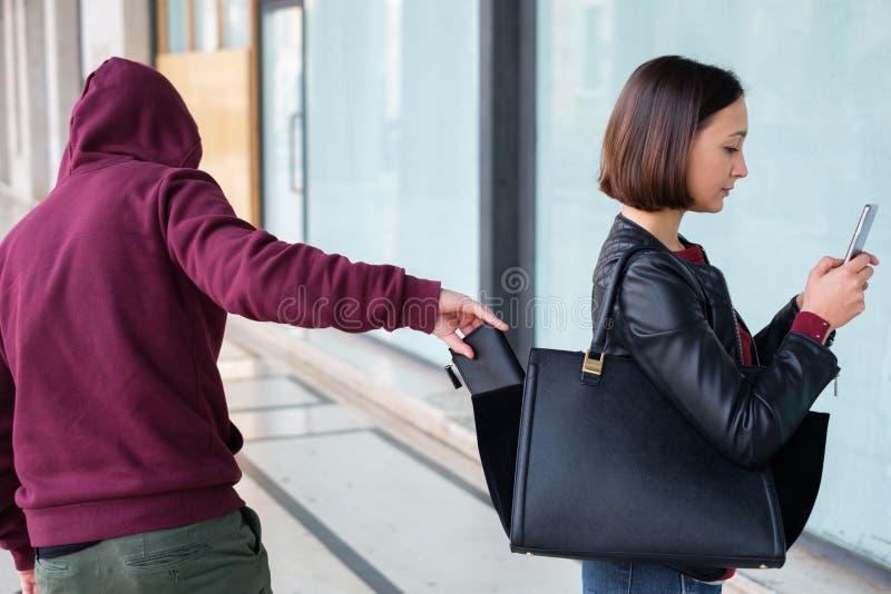 Voleur sélectionnant le portefeuille du sac d'une fille négligente photos stock