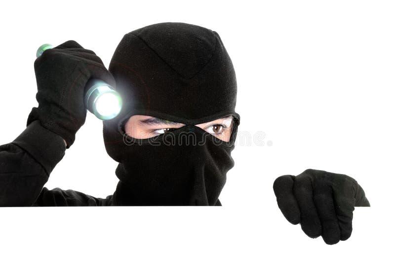 Voleur se cachant sous un mur blanc image libre de droits