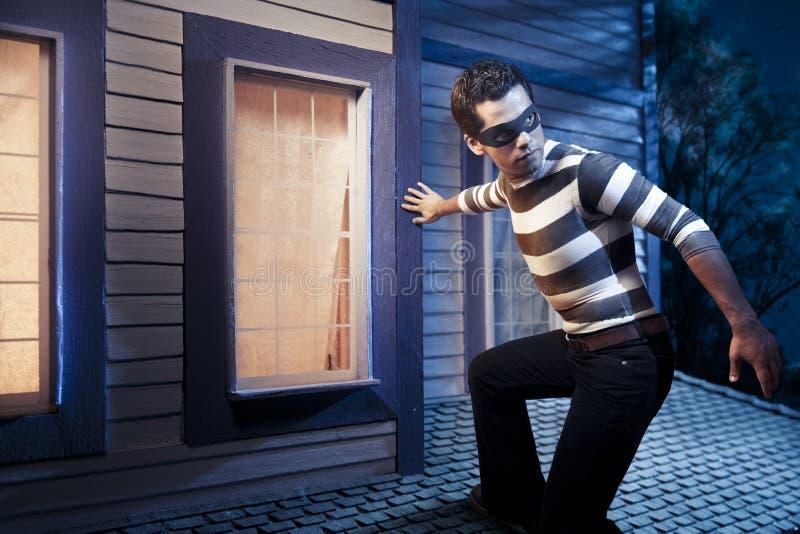Voleur sur le toit d'une maison la nuit image libre de droits