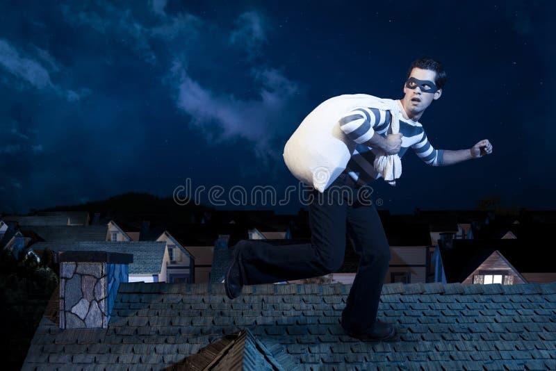 Voleur sur le toit d'une maison la nuit image stock
