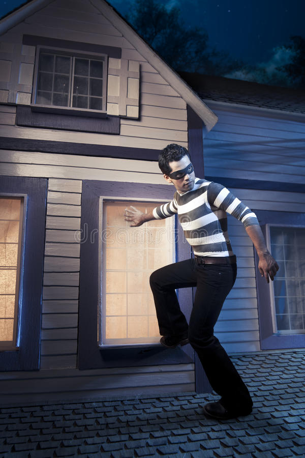Voleur sur le toit d'une maison la nuit photos stock