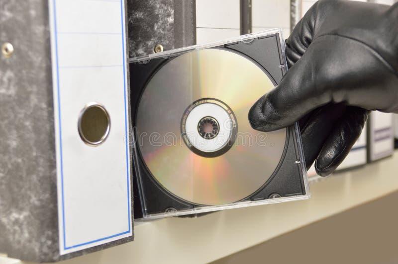 Voleur volant des documents dans le disque compact images stock