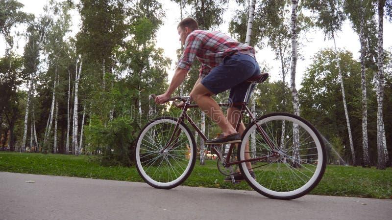 Volg aan jong knap personenvervoer een uitstekende fiets openlucht Het sportieve kerel cirkelen bij het park Gezonde actieve leve stock foto's