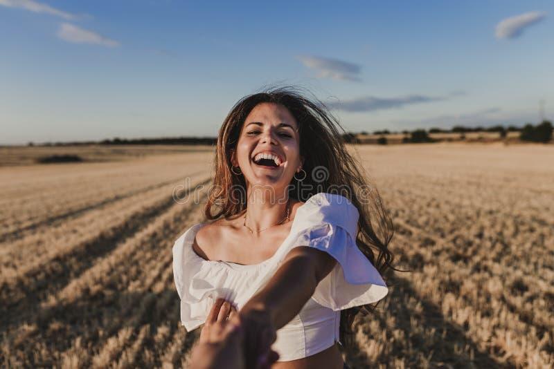 Volg me De jonge hand van de vrouwenholding en belangrijke man tot het mooie gele landschap van de aardzonsondergang Weergeven va stock fotografie