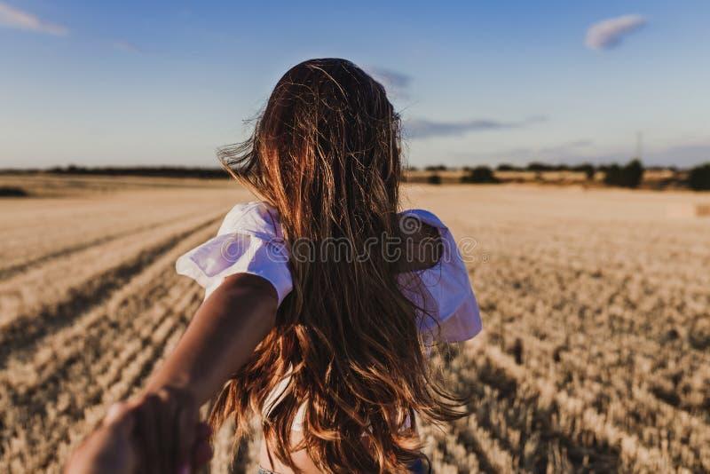 Volg me De jonge hand van de vrouwenholding en belangrijke man tot het mooie gele landschap van de aardzonsondergang Weergeven va royalty-vrije stock afbeelding