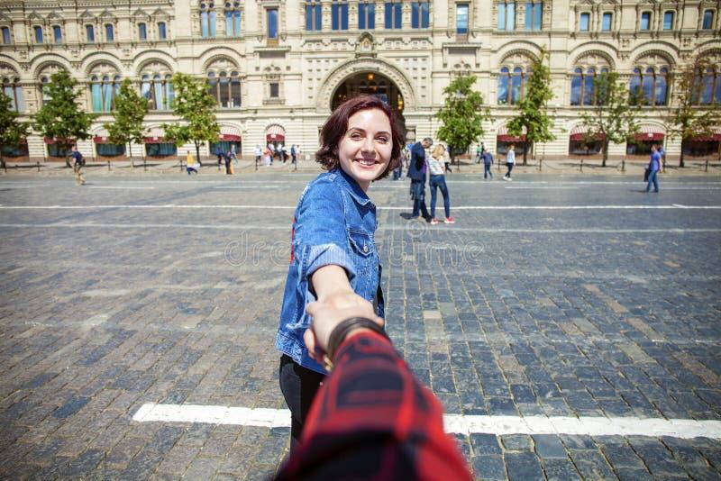 Volg me Het jonge gelukkige meisje trekt de kerelshand royalty-vrije stock foto's