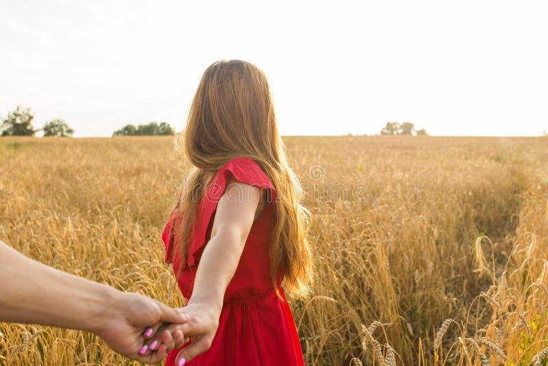 Volg me, houdt de Mooie jonge vrouw de hand van de mens op een tarwegebied stock afbeelding