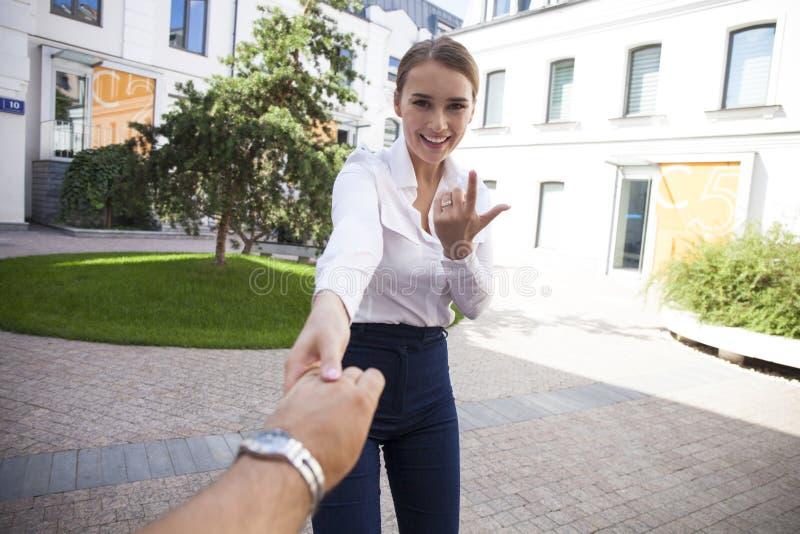 Volg me, houdt de Mooie jonge vrouw de hand van een man stock afbeelding