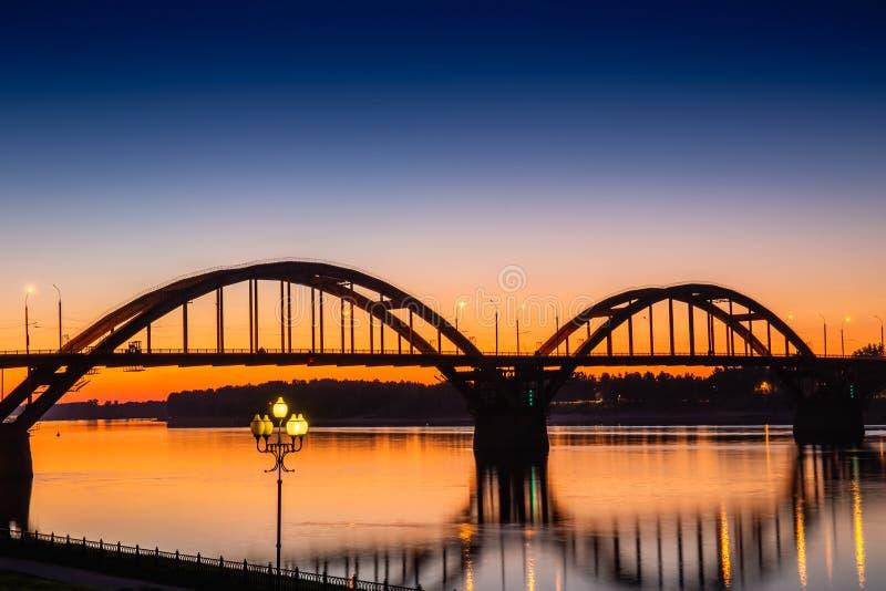 Volga brug over Volga rivier na zonsondergang met bezinning in water, Yaroslavl-de stad van het gebied, Rybinsk, Rusland royalty-vrije stock foto's
