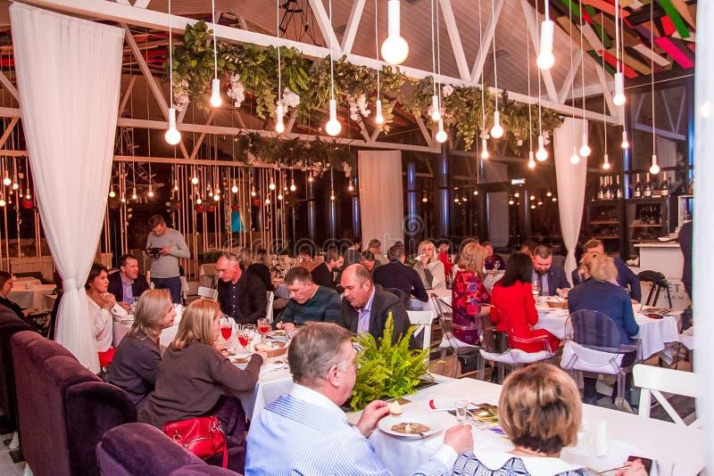 Volgograd, Russia - febbraio 2019: Molta gente pranza nel ristorante Indicatore luminoso luminoso immagini stock