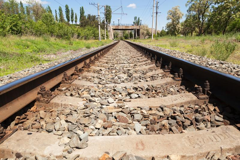 The railroad, rails for trains. VOLGOGRAD, RUSSIA - May 28, 2017: Railway rails and a way for trains against the background of the city bridge in are solar day stock image