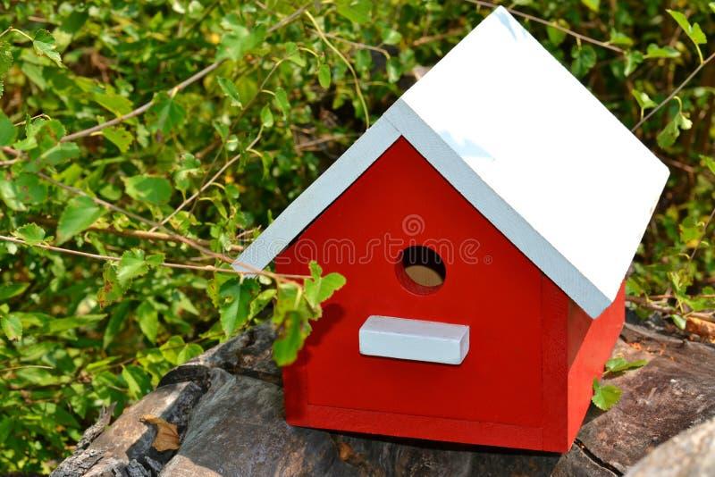 Volière rouge avec le toit blanc, se reposant sur un rondin images stock