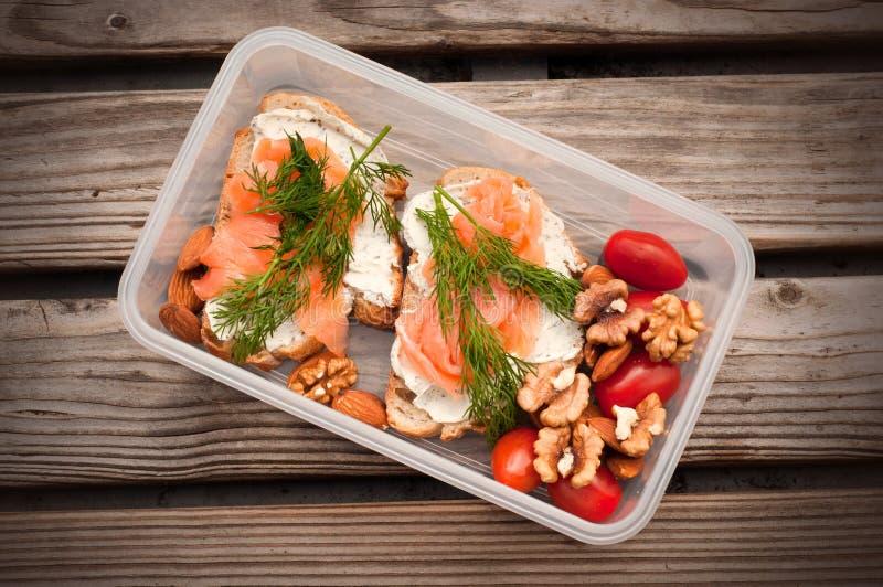 Volkorenbrood met kaas en zalm in een plastic container Dille en amandel met kersentomaten Gezonde sandwiches stock fotografie