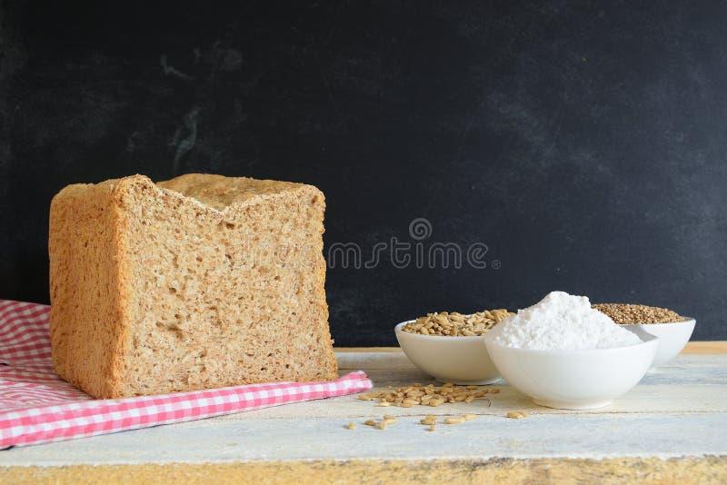 Volkorenbrood op een tafelkleed naast wat bloem en graangewassen tegen een bord royalty-vrije stock afbeelding