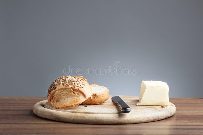 Volkorenbroodbroodje met karwijzaden, boter, mes stock afbeeldingen