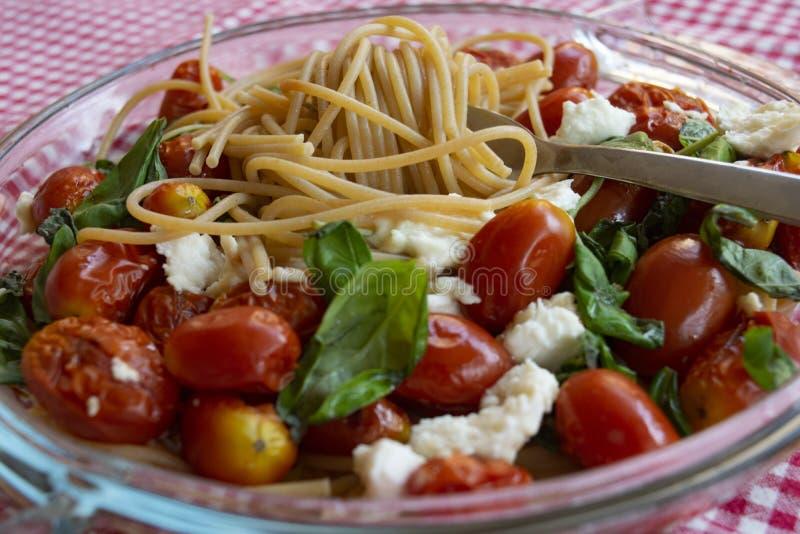 Volkorenspaghetti met tomaten en mozarella stock afbeeldingen