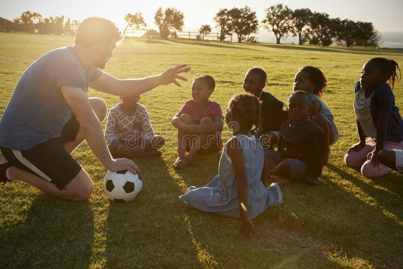 Volksschulekinder und -lehrer, die mit Ball auf dem Gebiet sitzen lizenzfreies stockbild
