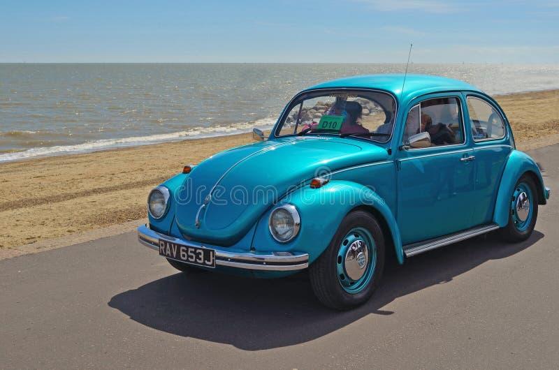 Volkswagen Beetle bleu classique étant conduit le long de la promenade de bord de mer de Felixstowe photos libres de droits
