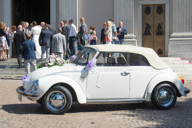 Volkswagen Beetle buiten kerk na huwelijksceremonie stock afbeelding