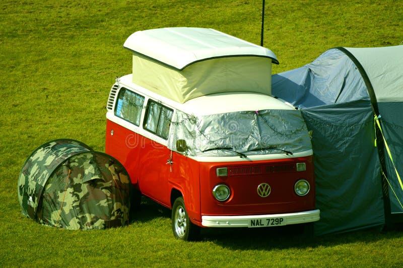 Volkswagen camper van camping in a field. Chester, England, UK, Europe - April 19, 2019 : An old Volkswagen camper van with modern tents camping in a field in royalty free stock photos