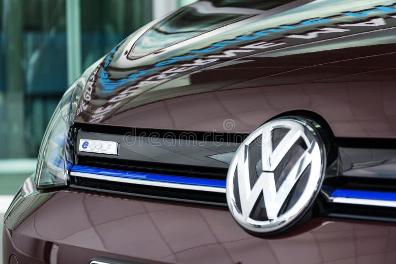 Volkswagen e-golf står den inkopplingshybrid- elbilen vid uppladdningsstationen royaltyfri fotografi