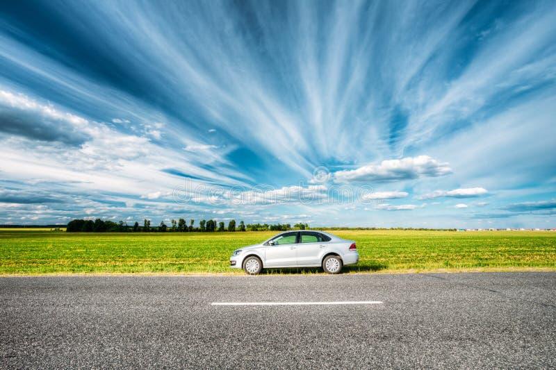 Volkswagen Polo Car Parking On een Kant van de weg van Landweg op een Achtergrond stock fotografie