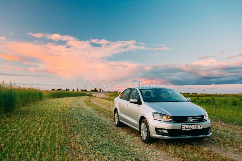 Volkswagen Polo Car Parking On Wheat fält Dramatisk himmel för solnedgångsoluppgång royaltyfria foton