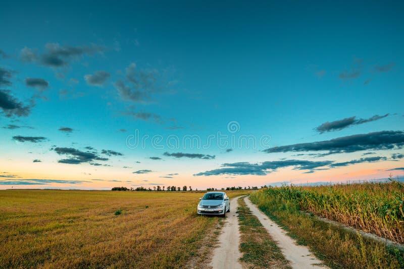 Volkswagen Polo Car Sedan Parking Near landsväg i sommarfält royaltyfri fotografi