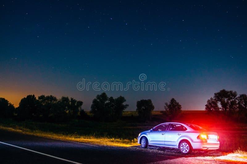 Volkswagen Polo på natten på vägrenen under den stjärnklara himlen D arkivbild