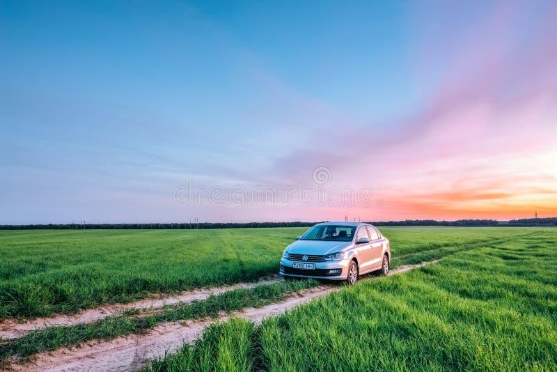 Volkswagen Polo Vento på en landsväg i ett fält på solnedgången in royaltyfria foton