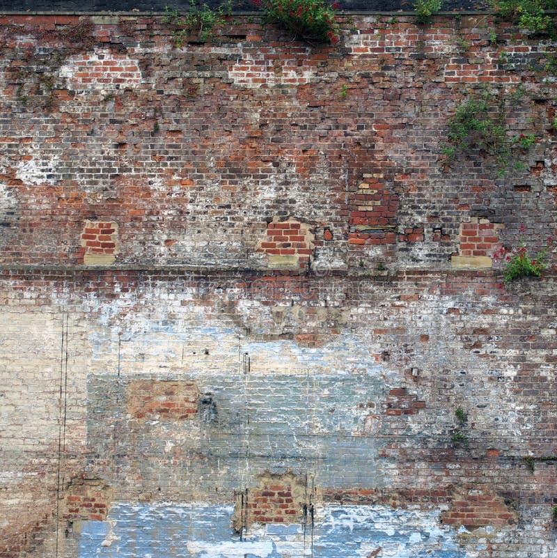 Vollbildbild einer sehr großen alten Ziegelwand mit vielen Flecken aus gepatchten und reparierten Teilen, Unkraut lizenzfreie stockfotografie