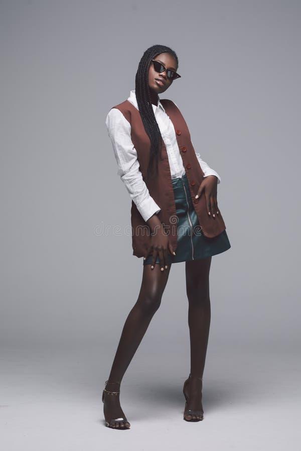 Volle Höhe der jungen zufälligen afrikanischen Frau in der Sonnenbrille und in hohen Absätzen lokalisiert auf grauem Hintergrund lizenzfreies stockfoto
