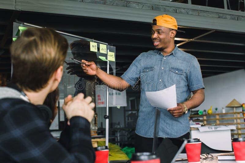Volle Konzentration bei der Arbeit Unternehmensteamarbeitskollegen, die im modernen B?ro arbeiten Afrikanischer Mann, der Darstel lizenzfreies stockfoto
