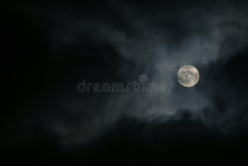 Volle maan achter de wolken stock fotografie