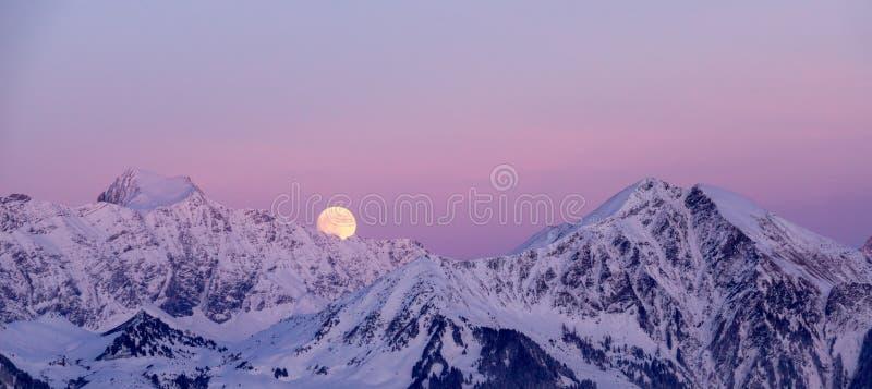 Volle maan die over bergen toenemen stock afbeeldingen