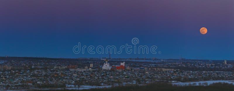 Volle maan die over de stad toenemen Zonsondergangtijd in de schemeringhemel Panorama van de Orthodoxe Kerk stock afbeelding