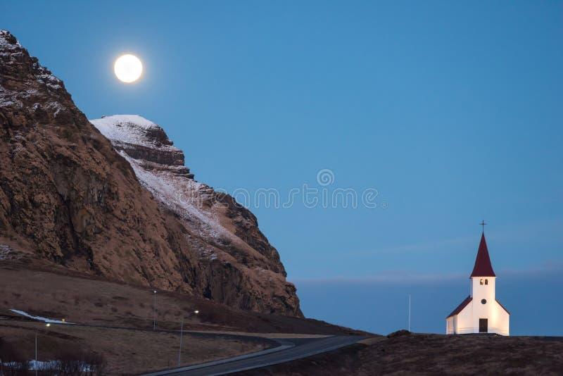 Volle maan die over Vik-kerk in IJsland toenemen royalty-vrije stock fotografie