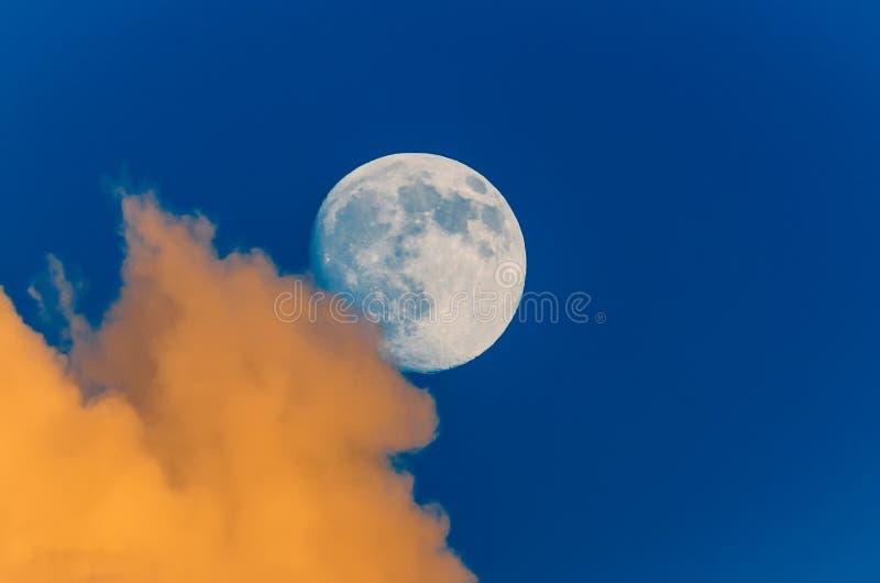 Volle maan die uit van achter de wolken, zonsonderganghemel gluren royalty-vrije stock foto's