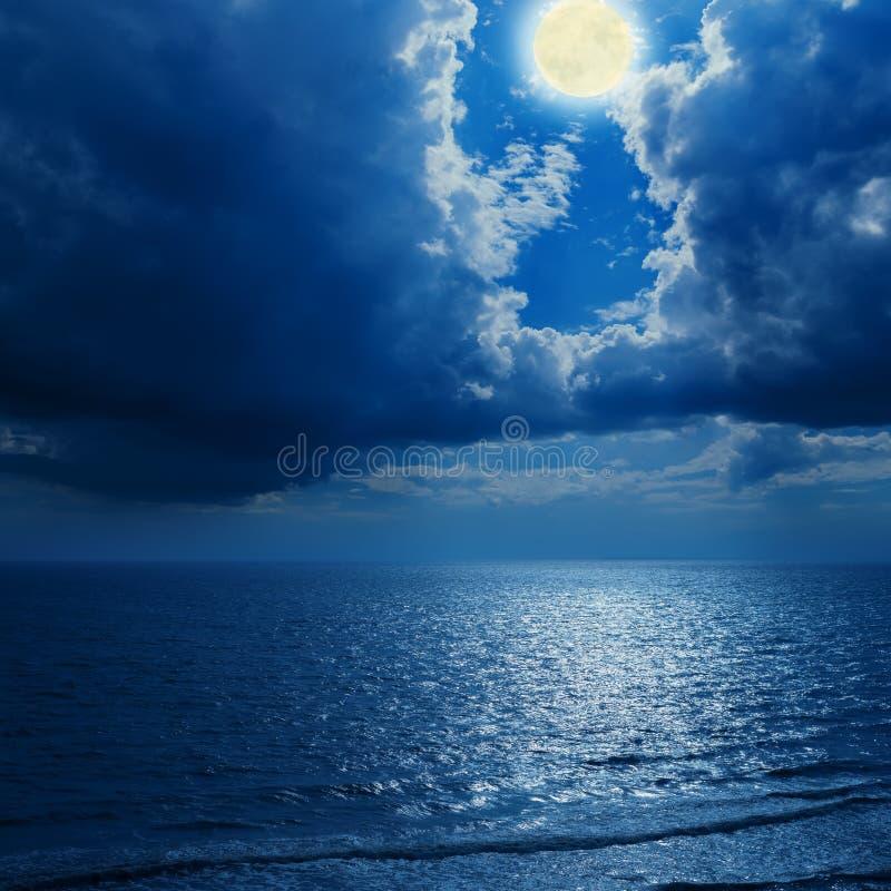 Volle maan in dramatische wolken en overzees stock afbeeldingen